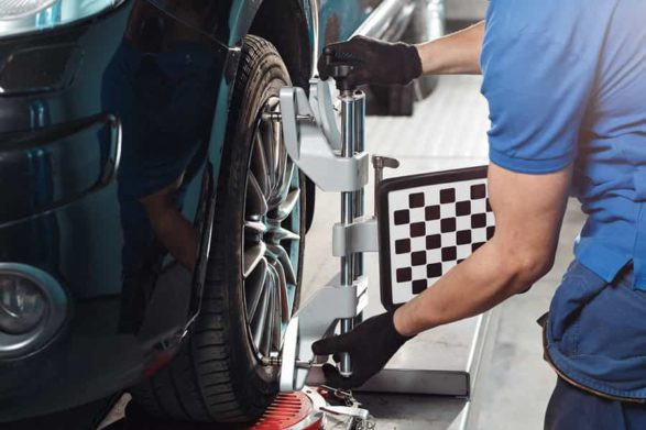 a mechanic fixing the alignment of a car tire