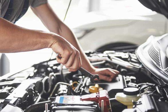 a mechanic does work on an engine under a car hood