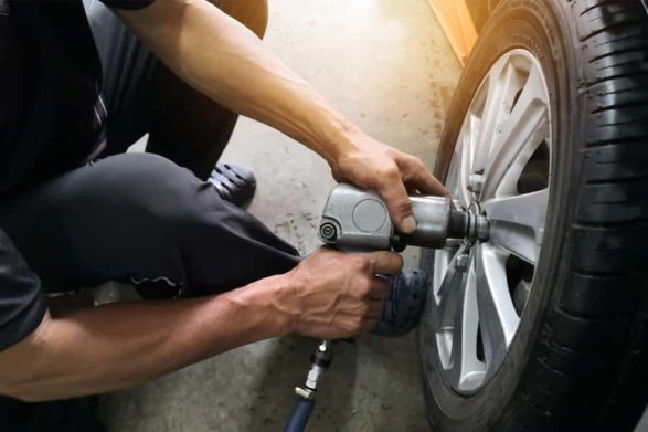 a mechanic readjucts the lug nuts of a car wheel