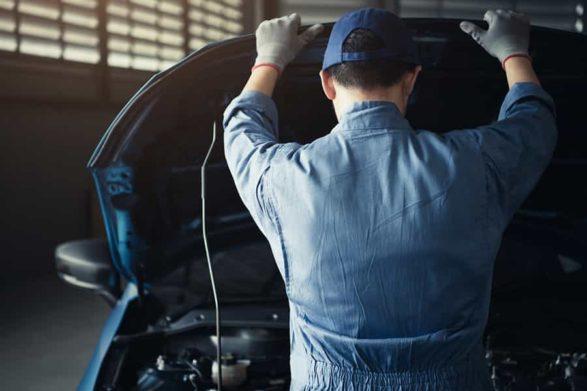 a mechanic raises a car hood to examine the engine