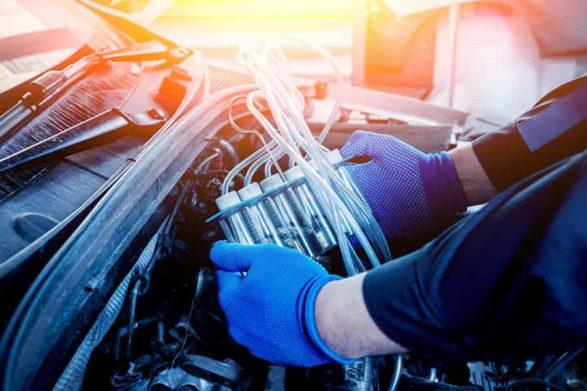 a mechanic holding fuel injectors under a car hood