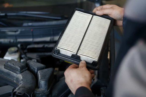 holding a air filter in front of a car engine