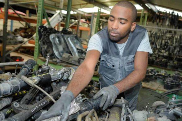 a mechanic examines an older car engine