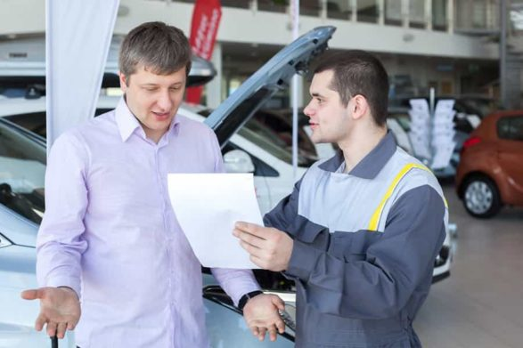 a mechanic explains a bill to a male customer who is unhappy