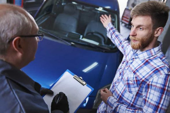 a customer motions to his car as he explains the problem to a mechanic