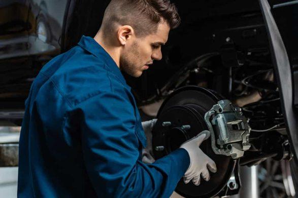 a mechanic repairs car brakes