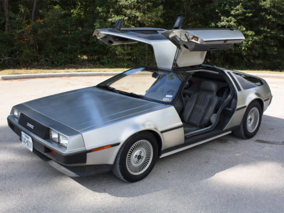 a silver dmc delorean with its gull-wing doors opened