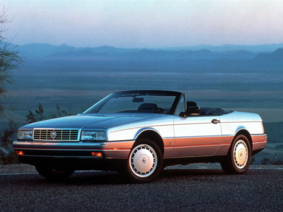 a silvery gray cadillac allante convertible with the top down