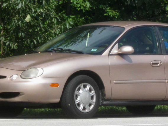 a shiny light copper colored ford taurus