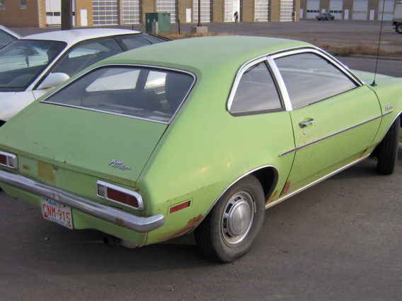 a lime green ford pinto parked in a space at a parking lot