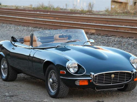 a black jaguar xk-e v12 series iii with its convertible top down and parked next to a railroad track
