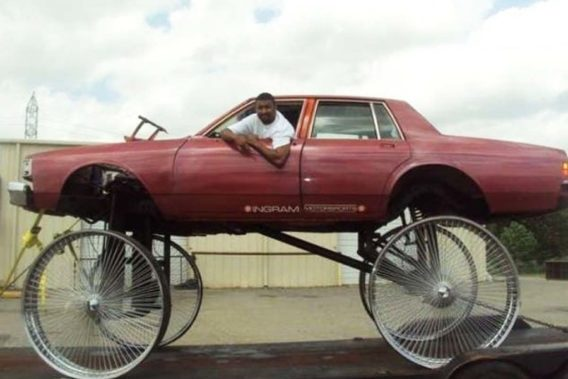 a man hanging out the window of his car on top of very tall thin rims with no wheels