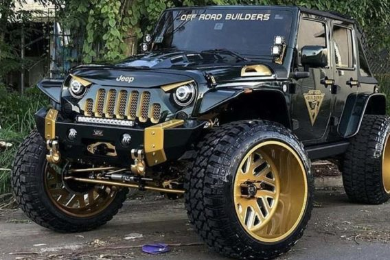 a black and gold jeep with headlights designed to make the front of the vehicle look like an angry face
