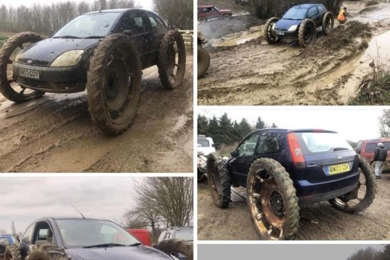 a small ford focus that is mudding with tires almost as big as the car itself