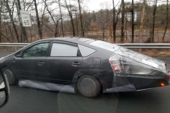 a car with plastic coverings duct taped on it as a DIY fix