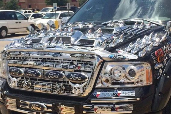 the hood of a ford truck completely covered in chrome stick ons and ford texas stickers