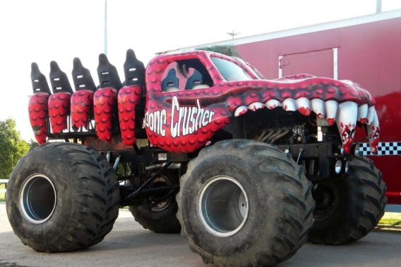 a lifted red truck with a hood shaped and painted to look like bloody teeth