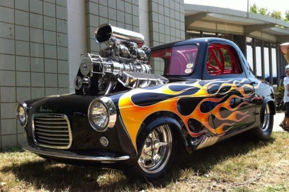 a retro car with a flame paint job and an oversized engine that sticks up out of the hood